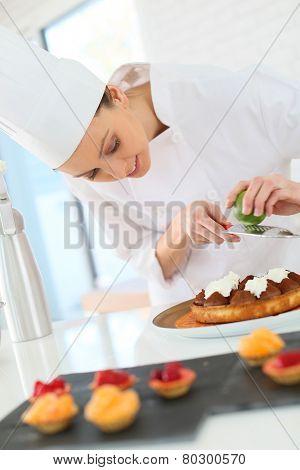 Pastry-cook shreding lemon zest over chocolate cake