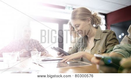 Young people in snack bar, connected on smartphone