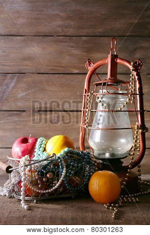 Kerosene lamp with beads and fruits on wooden planks background