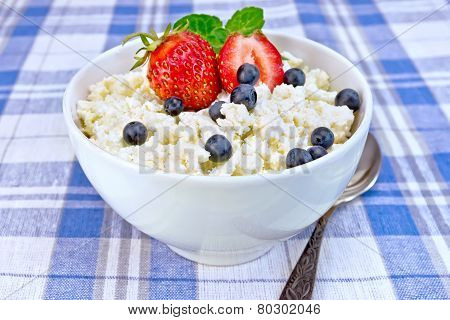 Curd in bowl with strawberries and blueberries on tablecloth