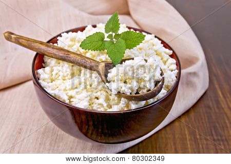 Curd in wooden bowl with spoon on napkin and board