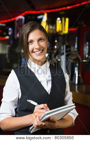 Happy barmaid smiling at camera taking notes in a bar