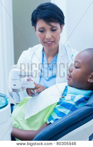 Female dentist showing young boy prosthesis teeth