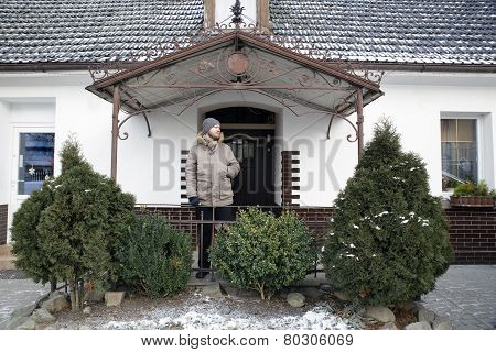 Man on a porch of white village house with green bushes ahead