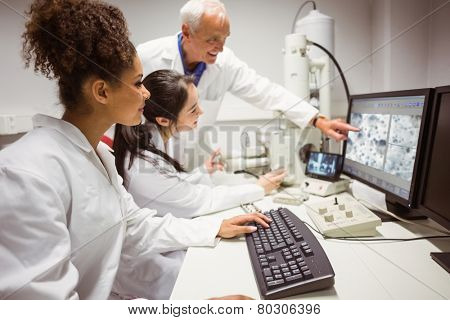 Science students looking at microscopic image on computer with lecturer at the university