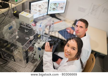 Biochemistry students using large microscope and computer at the university