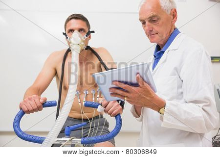 Doctor showing tablet pc to man doing fitness test at the medical centre