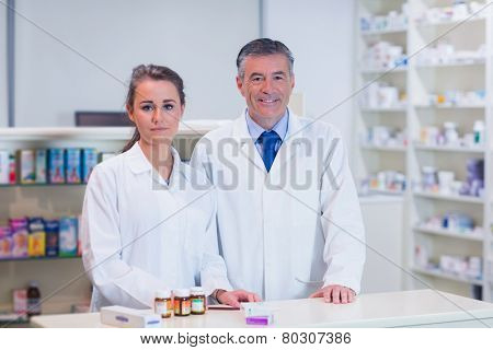 Pharmacist and his trainee looking at the camera in the pharmacy