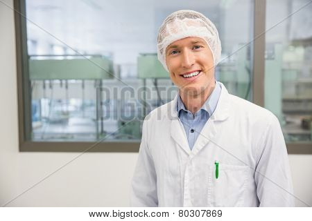 Happy pharmacist in a hairnet at the hospital pharmacy