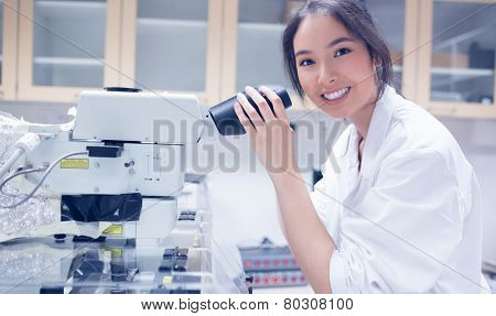 Pretty scientist smiling at the camera using microscope at the university