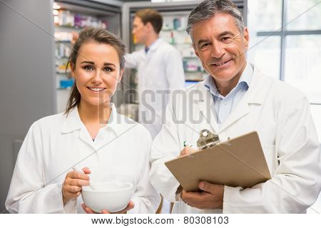Junior pharmacist mixing a medicine with her senior at the hospital pharmacy