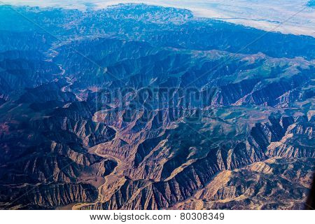 Aerial View of a Winding River Valley Through Mountains