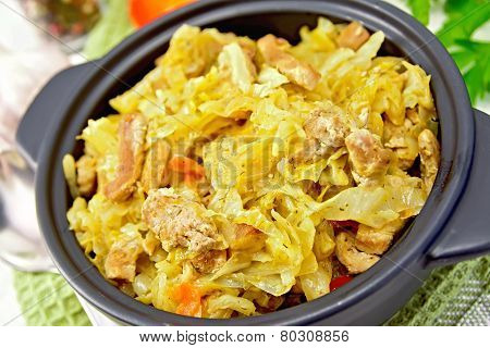 Cabbage stew with meat in black brazier on green napkin