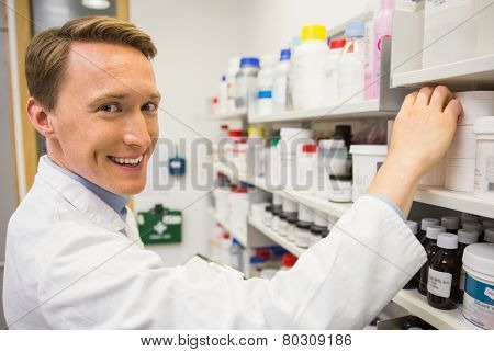 Handsome pharmacist taking medicine from shelf at the hospital pharmacy