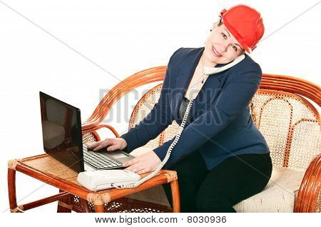The Girl In A Red Helmet With The Laptop Sits At A Table And Calling By Phone. Isolated On White Bac