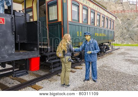 MOLLENDO, PERU, MAY 19, 2014:  female tourist shakes hands with a wax statue of rail worker in Ferro Carilles del Sur train open air museum