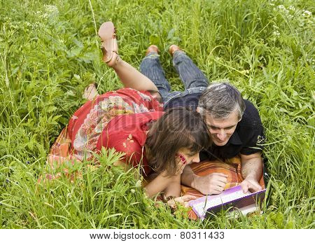 Couple With Notebook On Grass
