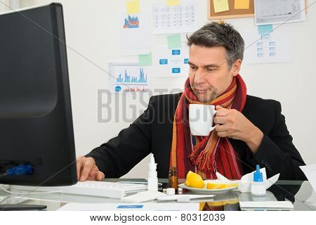 Sick Businessman Using Computer Holding Cup