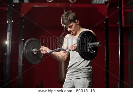 Young Man Lifts Weight In Gym