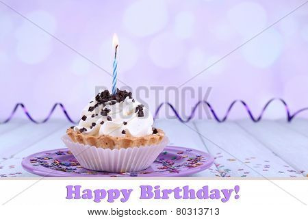 Birthday cup cake with candle and sparkles on plate on color wooden table and light background