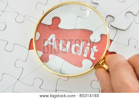 Person Holding Magnifying Glass Over Audit Text