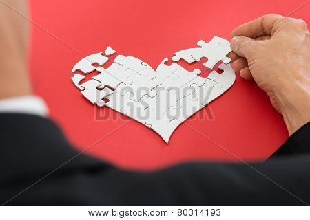 Person Solving Heartshape Jigsaw Puzzle