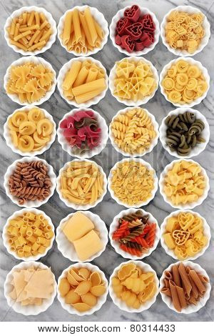 Pasta dried food selection in white porcelain crinkle bowls on marble background.