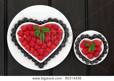 Blueberry and strawberry super food fruit in heart shaped and round dishes with leaf sprigs.