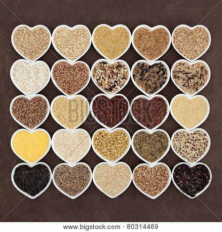Large grain and cereal food selection in heart shaped porcelain bowls over lokta paper background.