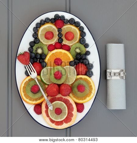 Fruit selection for antioxidant health food diet on an oval plate with old silver fork and napkin with ring over   wooden grey background.