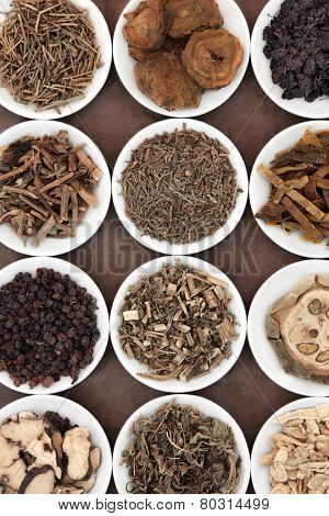 Chinese herbal medicine selection in porcelain bowls over brown paper background.