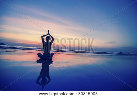 Lady practicing yoga on the ocean side, the silhouette of awesome sunset.