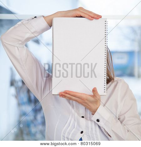 Woman holding blank ring-bound notebook