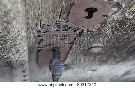 Run-down wooden door and decorated iron lock with crosses