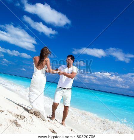 Happy Newlyweds Having Fun On Beach