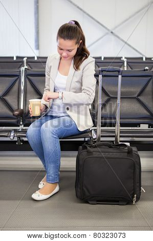 Businesswoman Checking Time At Airport Lobby