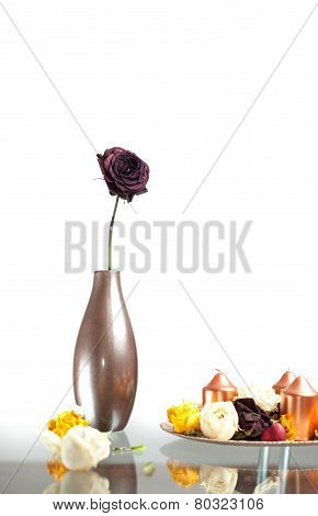 Metallic vase with one rose flower on the table over white. Modern decoration with vase, flowers