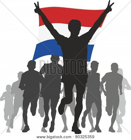 Athlete with the Netherlands flag at the finish
