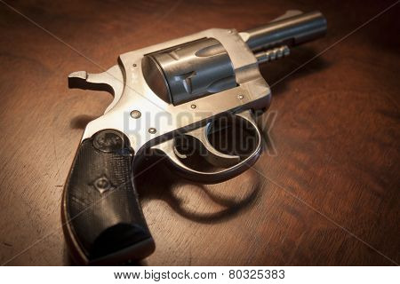 MARYLAND, USA - CIRCA DEC 2014: A staged close-up of an H & R .32 caliber pistol on a brown wooden table, shallow depth of field.