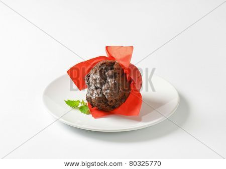 dark chocolate muffin in the red paper basket, sprinkled with sugar