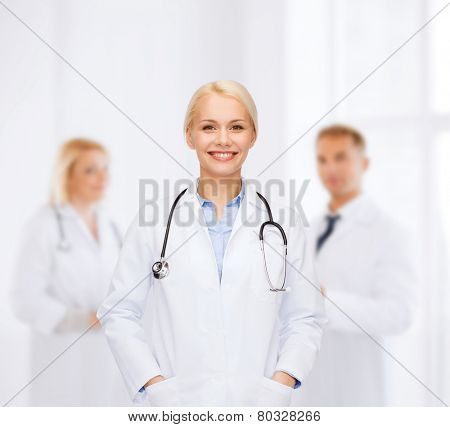 healthcare and medicine concept - smiling female doctor with stethoscope over background with group of medics in hospital