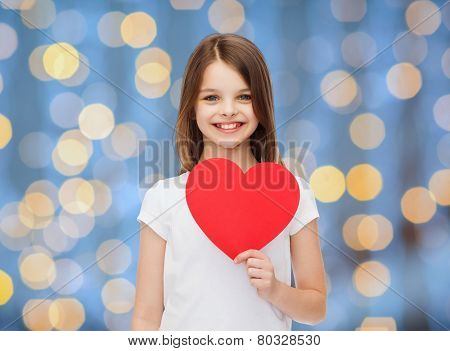 love, charity, holidays, children and people concept - smiling little girl with red heart over blue lights background