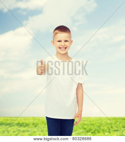 advertising, people, summer and childhood concept - smiling little boy in white blank t-shirt showing thumbs up over natural background