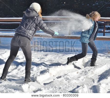 Two Women Playing In The Snow.