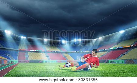 Football player at stadium sliding to kick the ball