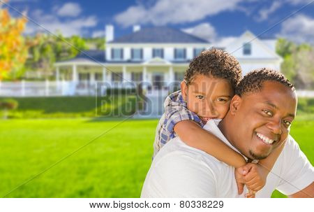 Happy Playful African American Father and Mixed Race Son In Front of House.