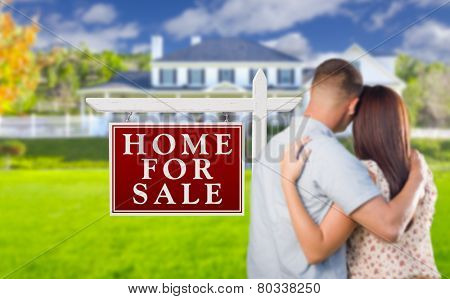 For Sale Real Estate Sign and Affectionate Military Couple Looking at Nice New House.