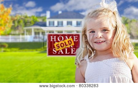 Cute Smiling Girl in Front Yard with Sold For Sale Real Estate Sign and House.