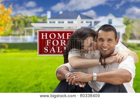 Young Happy Hispanic Young Couple in Front of Their New Home and For Sale Real Estate Sign.
