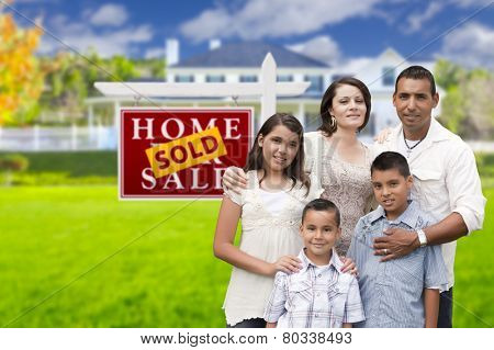 Happy Hispanic Family in Front of Their New House and Sold Home For Sale Real Estate Sign.
